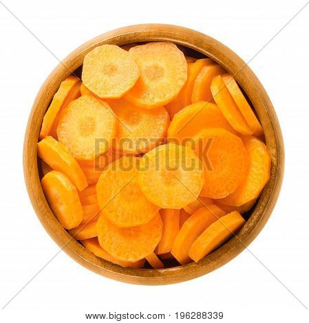 Carrot slices in wooden bowl. Fresh cut crisp slivers of Daucus carota, a root vegetable with orange color. Edible taproot pieces. Isolated macro food photo close up from above on white background.