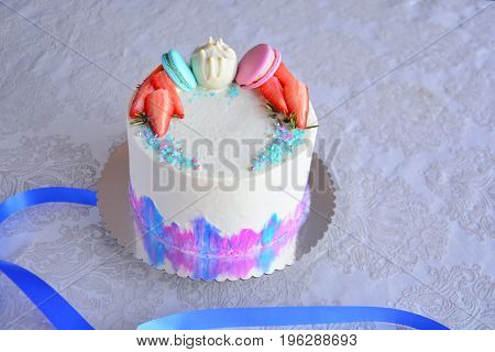 White cake with blue and pink macaroons white cake pops strawberries and red fruits