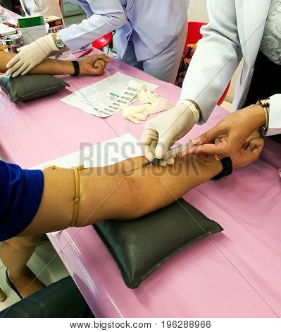Nurse drawing blood sample from arm patient for test