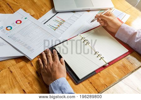 Businessman Holding A Pen For Working On His Plan Project