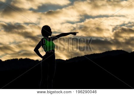Silhouette Young Asian Woman In Sportswear Pointing At The Mountain
