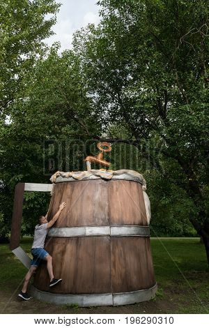 The guy hugs a huge wooden beer mug in the city park.