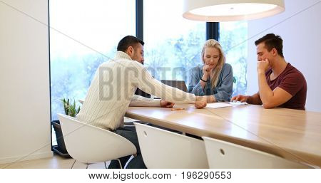 Young rich couple buy an apartment, property, house,  enter into a contract with a realtor. Signs an agreement with the seller