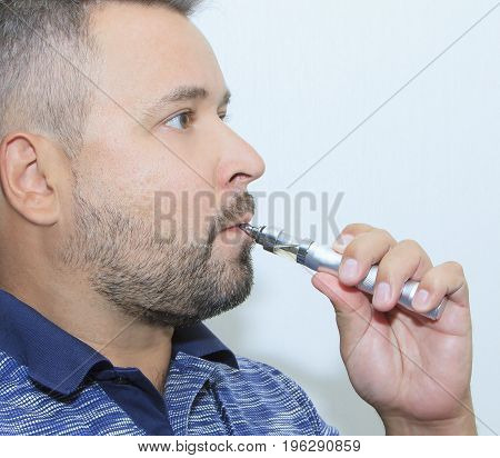 Profile view of young man smoking electronic sigarette
