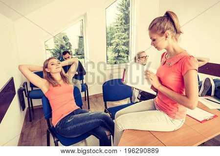 Highschool students having fun during a break in classroom interior girl reading book classmates in the background