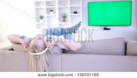 Young beautiful girl enjoying music through headphones, laying on sofa at home