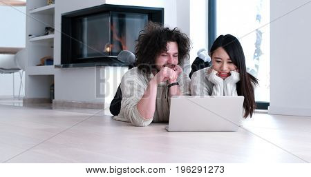 Young beautiful multiethnic couple using a laptop and doing shopping online at home on the floor