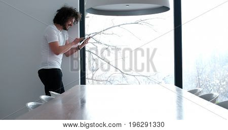 Handsome casual young man using a tablet at luxurious home