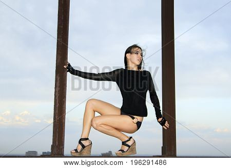 Young girl posing on the rusty structures over blue sky