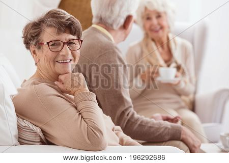 Happy elderly lady enjoying time spent with her family by a cup of tee