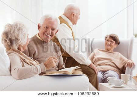 Elderly friends at resting home enjoying time drinking tee talking and reading