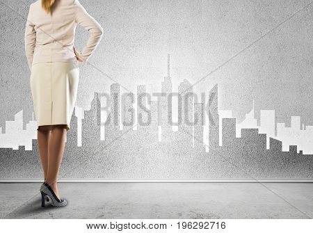 Bottom view of businesswoman and sketches of construction project on wall