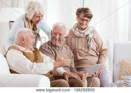 Elderly couples using technology while enjoying each others company