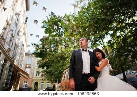 Awesome Newly Married Couple Walking, Posing And Having Fun In The Park With Hippie Van On The Backg