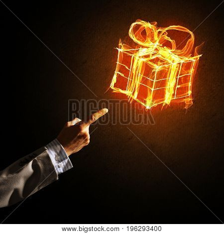 Businessman hand pointing at glowing fire gift box icon on dark background