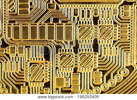 Abstract background : Golden electronic circuit macro photo. Image taken from gold plated coin stamped in form of electronic circuit as normally seen in PCB (Printed Circuit Board).