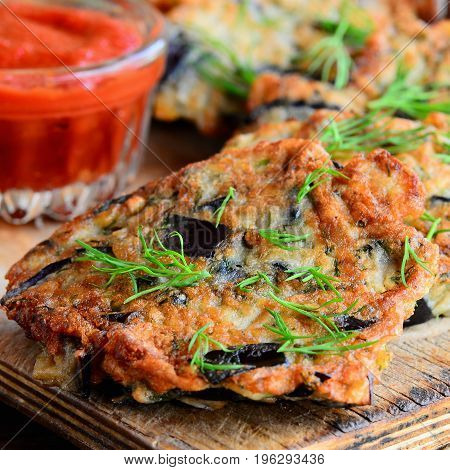 Simple fried eggplant cutlets with garlic and dill on a white plate and a vintage wooden table. Tomato ketchup sauce in a glass bowl. Veggie eggplant cutlets idea. Closeup