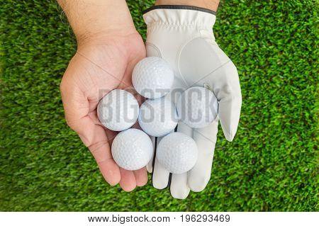 Hands holding 6 golf balls one hand wearing golf glove : with green grass background.