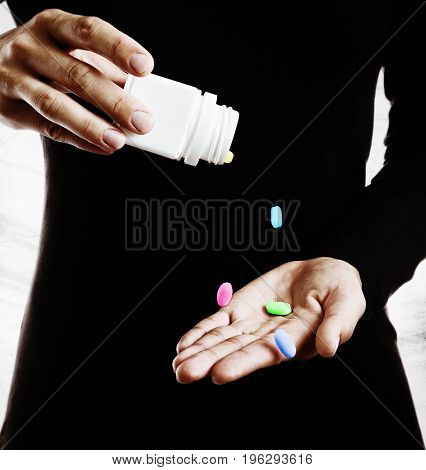 The concept of narcotic addiction. Multicolored pills fall on the female palm.