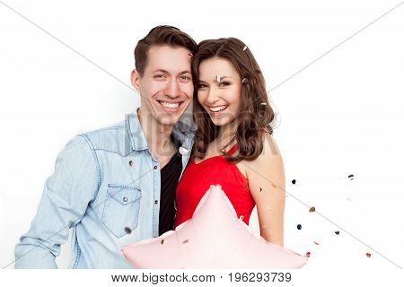 Young laughing couple holding balloon and posing on white in falling confetti.
