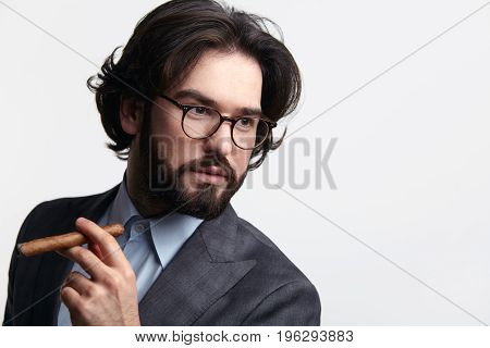 Young bearded man in elegant suit posing with cigar on white background.