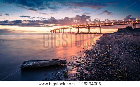 Sea shore night landscape. The Gulf of Finland. Bridge over the bay in St. Petersburg