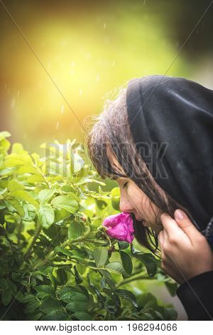 happy girl breathing in the park on a rainy day inhaling the smell of a flowering bush