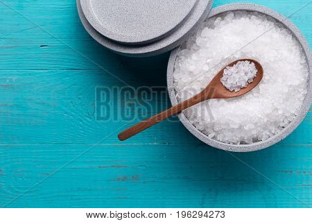 Sea salt in an stone bowl with small wooden spoon on a blue wooden table