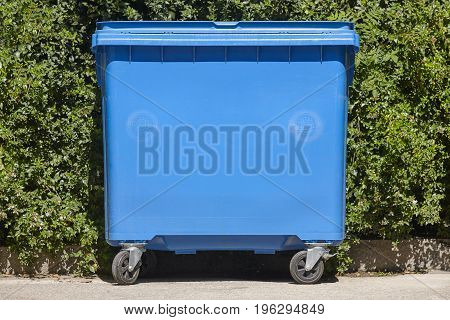 Blue recycling container for paper with green bush background. Environment.