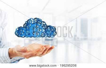 Close of businessman holding in palms cloud of gear mechanism