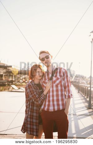 man and woman in the plaid shirt hugging on the background of the city.