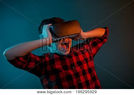 Amazed little boy touching the headset during the VR experience.