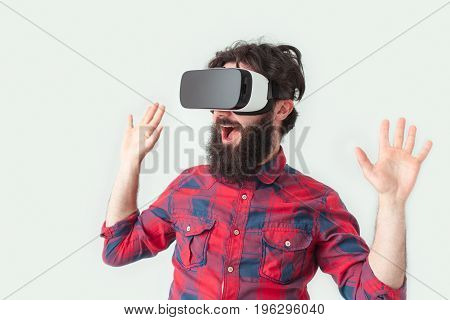 Young bearded man in VR glasses holding hands up in gesture of surprise.