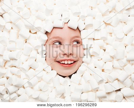From above view of happy kid all covered with white marshmallows and looking away.