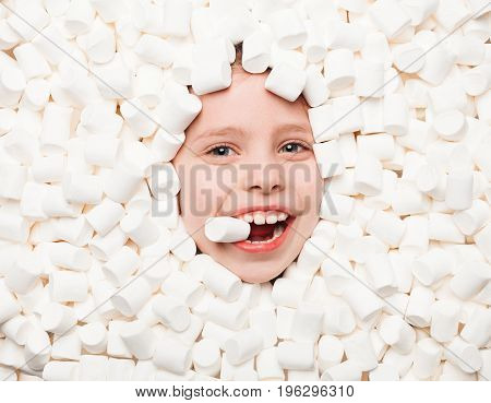 From above view of child face covered with white fluffy marshmallows and looking at camera.