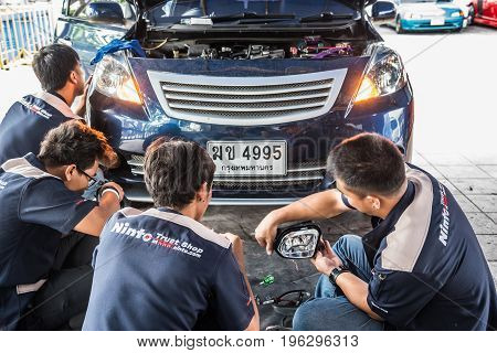 Checking A Car Headlight For Repair At Car Garage