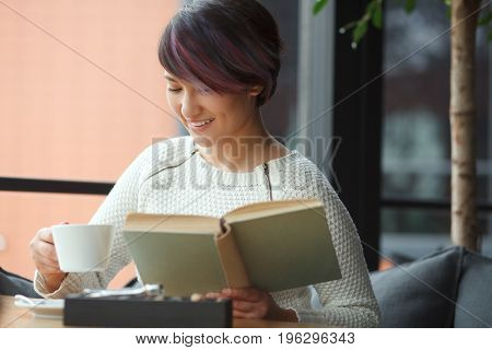 Nice girl holding cup of coffee while reading hilarious story in book on cafe