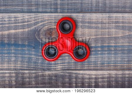 Red spinner lies in the middle of a wooden table