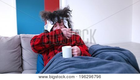 young Handsome sick man is holding a cup while sitting on couch covered in plaid