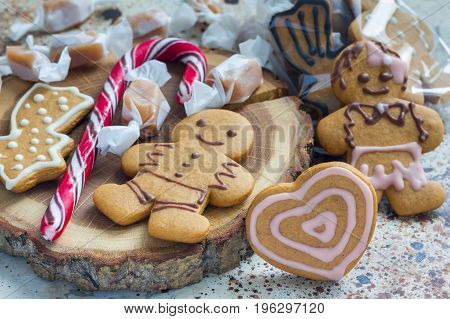 Sweet gifts for holiydays. Homemade christmas gingerbread cookies and caramel candies on wooden board horizontal