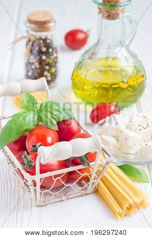 Summer pasta ingredients. Cherry tomatoes basil feta cheese spaghetti and olive oil on a white wooden background vertical