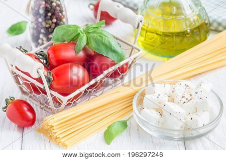 Summer pasta ingredients. Cherry tomatoes basil feta cheese spaghetti and olive oil on a white wooden background horizontal