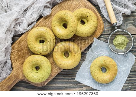 Freshly baked gluten free matcha banana donuts on wooden board horizontal top view