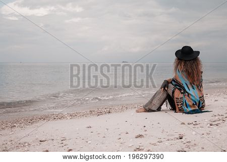 Fashionable young woman wearing in hat and poncho sitting on beach and watch the sunset