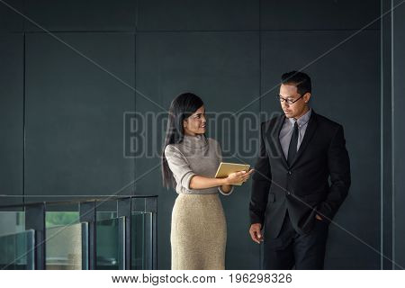 Young Asian businessman and beautiful secretary working in office selective focus