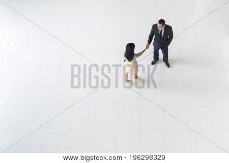 Top view Asian business people man and woman greeting by smiling and shaking hands copy space