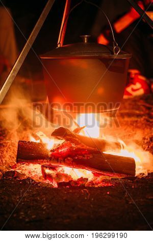 boiling pot over an open fire on a blurred background.