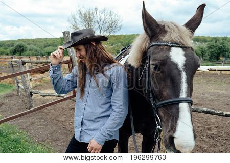 Young Man With Long Hair In Hat Standing Near Horse On Countryside And Holding His Hat