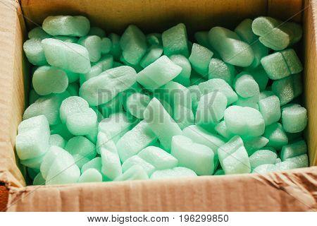 pieces of green styrofoam in carton box.