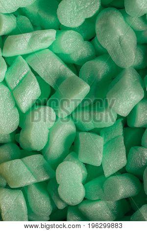 pieces of green styrofoam in carton box background.